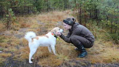 Nainen ja metsästyskoira metsän laidassa.