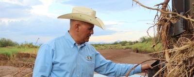 En man i blå skjorta, gröna byxor och äggskalsfärgad cowboyhatt inspekterar en stålkonstruktion.