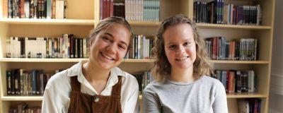 Elin Fierens och Anna-Sofia Paavonen sitter framför bokhyllor fulla med böcker.