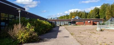 Tom skolgård vid en skolbyggnad i rött tegel.