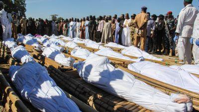 Sörjande bybor samlades runt de insvepta kropparna under söndagens begravning i Zabarmari.