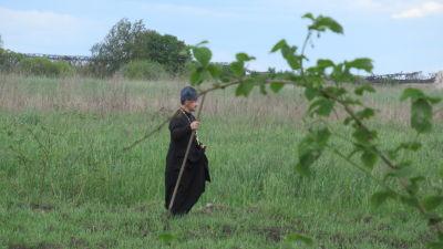 En präst vandrar på en odlingsplätt.