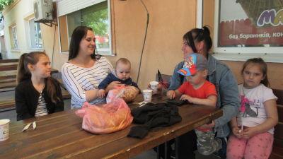 Två kvinnor och fyra barn sitter vid ett träbord på en uteservering.
