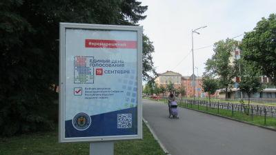 En reklamskylt som uppmanar människor att rösta i det ryska valet. Skylten finns på ett parkområde. I bakgrunden kan man se en kvinna med en barnvagn.