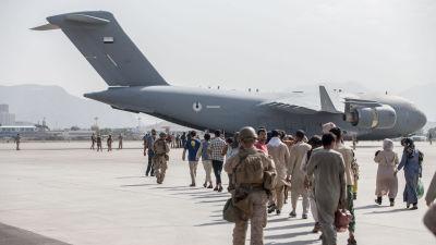 Människor på flygfältet i Kabul går mot en Air Force Boeing C-17 för att evakueras. Soldater går bredvid.