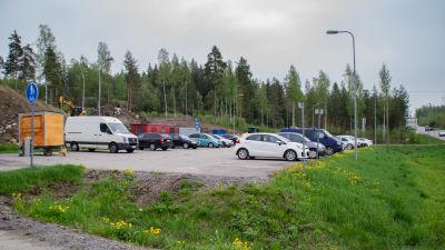 Bilar på en parkeringsplats intill en väg.