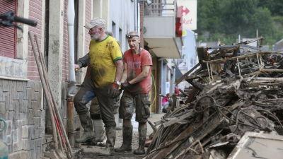 Två volontärer deltar i röjningsarbeten utanför ett ödelagt hus.