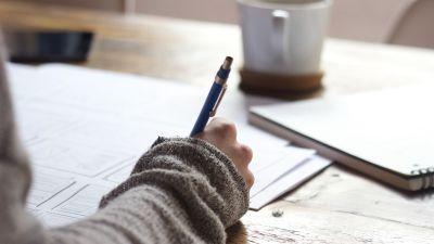 Handen på en person som sitter och studerar.