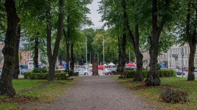 Monumentparken i Lovisa. På bilden syns ett esplanadområde, med en grusväg i mitten kantad av stora lövträd. I ändan syns ett monument i sten.