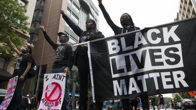 Maskerade black lives matter protestanter som bär på plakat och flaggor