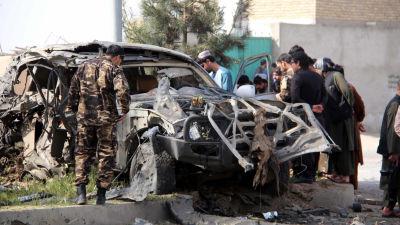 Sotilaat ja siviilit tutkivat autopommin jälkiä Afganistanissa.