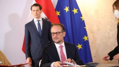 Mies istuu pöydän ääressä, taustalla seisoo toinen mies