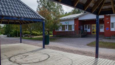 I förgrunden syns svarta cirklar gjorda med moped på en träterrass. I bakgrunden ett trähus med skylten Pleissi på väggen.