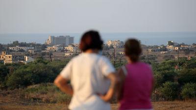 Två grekcyprioter från Varosha står på den cypriotiska sidan om gränsen och tittar på Varosha.