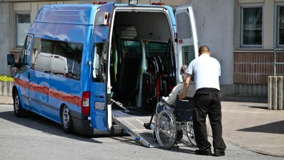 En person i rullstol rullas in i en taxibil.