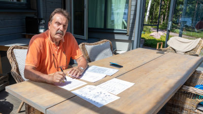Lasse Wikholm vid ett trädgårdsbord.