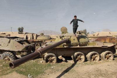 En afghansk pojke står på det som finns kvar av en stridsvagn från sovjeteran