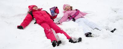 Två barn ligger i en snöhög på rygg. De skrattar.