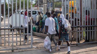 Migranter går igenom en port.