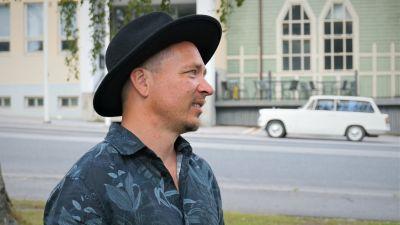 Man i svart hatt står vid en gata.