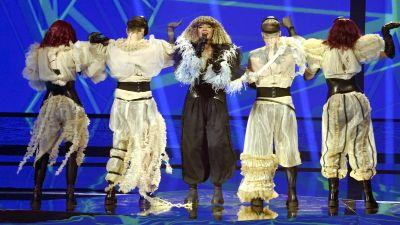 Kvinna på scen omgiven av dansare