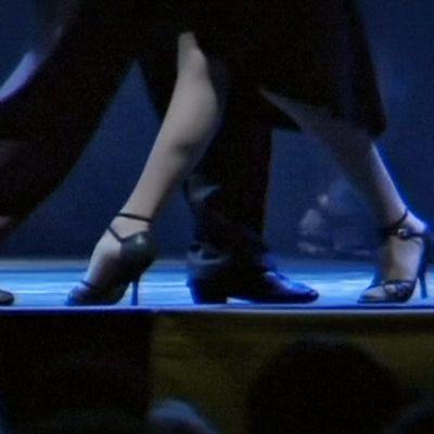 Mies ja nainen tangon pyörteissä esiintymislavalla.