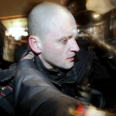 Venäläiset poliisit taluttavat oppositiojohtaja Sergei Udaltsovia Moskovassa.