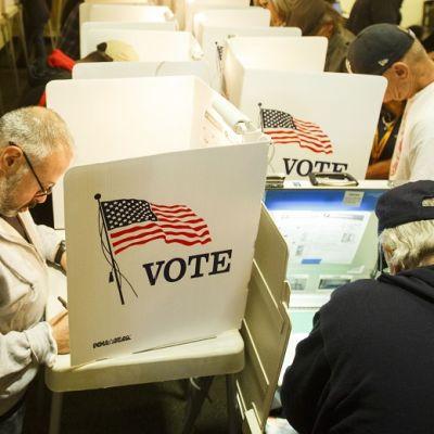 Äänestäjät syventyneinä täyttämään vaalilippujaa.