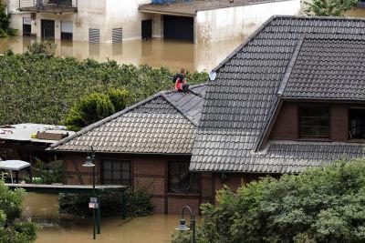 Kvinna sitter på taket till ett hus. Vattennivån omkring husen är hög.
