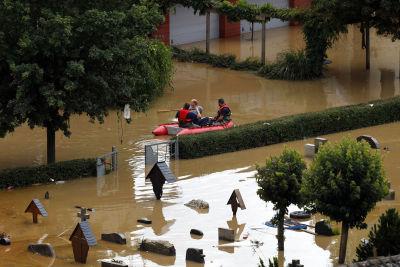 Tre personer i en liten gummibåt paddlar i översvämningsområdena vid en kyrkogård.