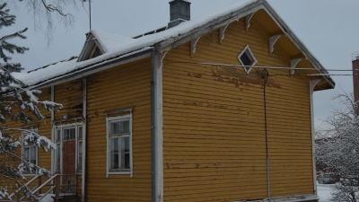 En gul trävilla, gammal arbetarbostad med fler bostäder. Målfärgen flagar, stockarna är ruttna vilket lett till hål i ytterväggarna.