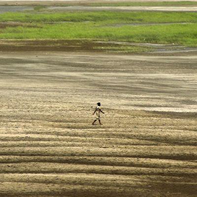 Mies kävelee kuivaa jokivartta, jossa hiekka aaltoilee.