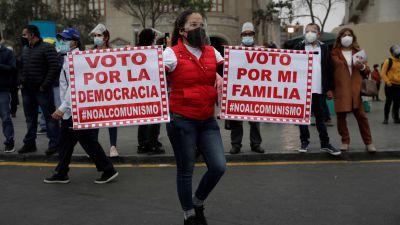 En peruansk demonstrant håller upp plakat där det står en uppmaning om att stöda demokrati och inte kommunism.