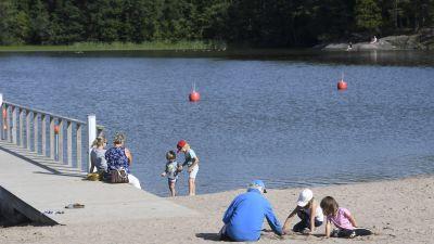 Barn och vuxna umgås på stranden vid Bodom träsk i Esbo.