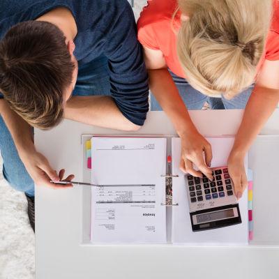 Man och kvinna sitter vid ett bord med en kalkylator och eknomiska papper.