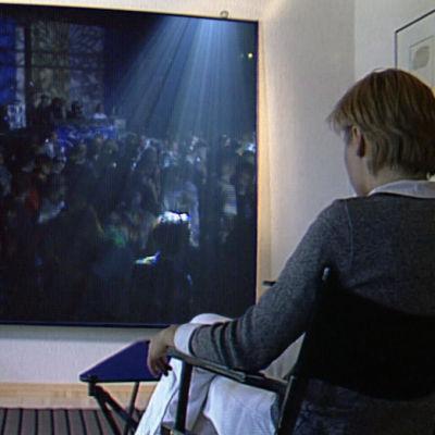 Nainen katsoo seinänkokoiselta näytöltä kuvaa bileistä, 1994.