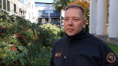 Niklas Guseff, en man med grånande hår och en Gränsbevakaruniform, står på en gård med höstgula träd.
