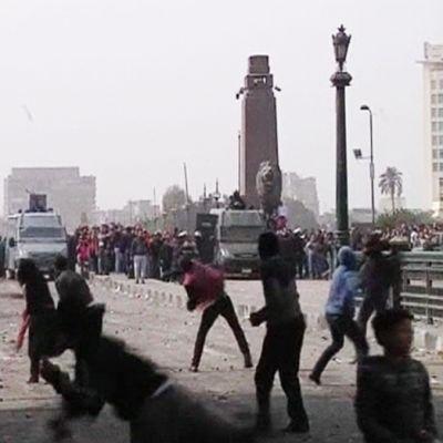 Mellakoitsijat heittelivät kiviä poliisiajoneuvoja kohti Tahririn aukiolla Kairossa 27. tammikuuta.