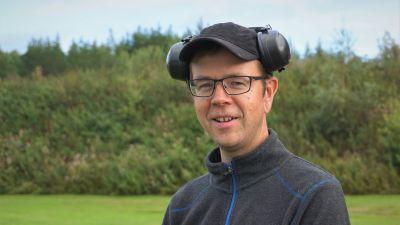 Man i glasögon och keps med hörselskydd på huvudet ler mot kameran.