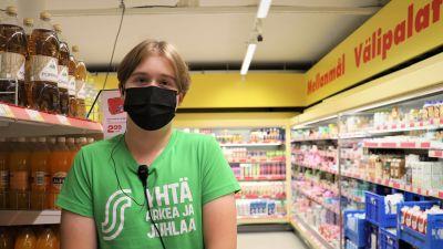 Kasper, sommarjobbare på Sale i Nagu, står i butiken iförd en grön t-skjorta.