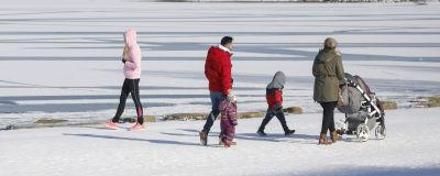 En familj ute på promenad i vinterväder.