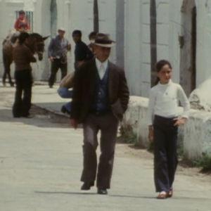 Mies ja tyttö kävelee kadulla. Taustalla ihmisiä.