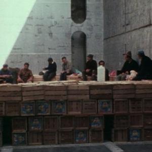Miehet pitävät taukoa laivan ruumassa laatikoiden päällä.