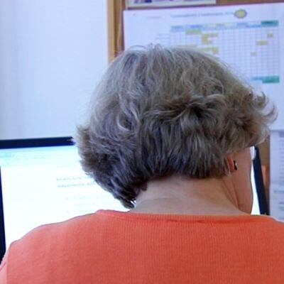 Noin kuusikymppinen nainen tietokoneen äärellä toimistossa.