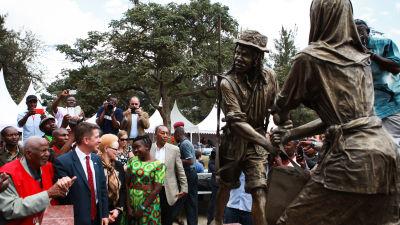 Ett monument föreställande två människor avtäcks. Runtom står en folkskara.