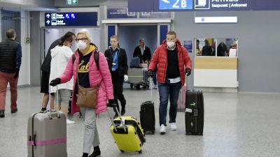 Resenärer som drar på resväskor och bär andningsskydd.