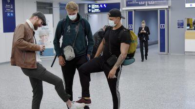 """Tre unga män hälsar genom att """"skaka fot"""" med varandra på Helsingfors-Vanda flygplats."""