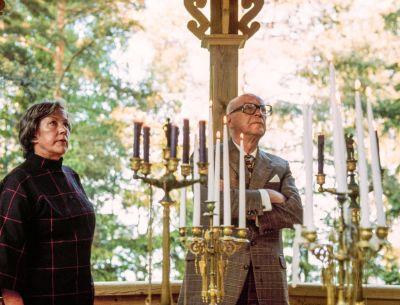 Tekstiilitaiteilija Armi Ratia ja presidentti Urho Kekkonen ihastelevat kynttiläkruunuja verannalla kesäisessä maisemassa. Kuva Bökarsin kartanosta Porvoosta.