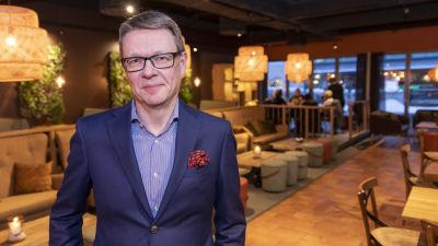Timo Lappi i kostym i en restaurang.