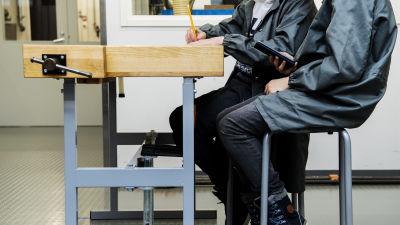 Två högstadieelever sitter vid ett slöjdbord.